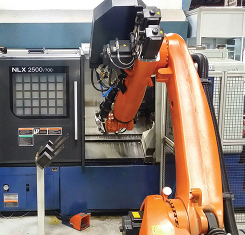 A robot loading parts to a machine at Tremec